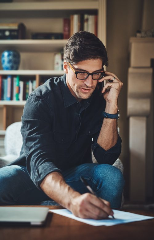 Shot of a handsome young businessman making a phone call while working in his office at home